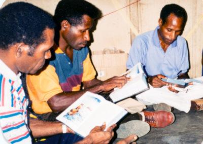 Essau, Sakarias, and Kori read their New Testaments