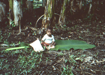 Kori playing on banana leaf while his mom pounds sago