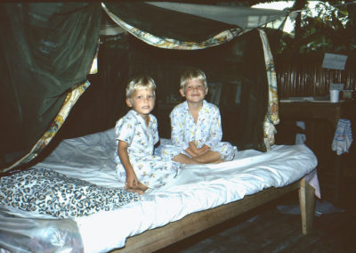 Scotty and David under mosquito net Aunt Sally made for them